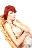 портрета модели волос красотки усаживание женского красное Стоковая Фотография