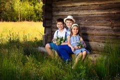 Портреты друзей, сидя около деревянной стены сарая стоковые фото