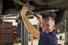 Портрет автоматического механика работая под автомобилем в гараже стоковое изображение