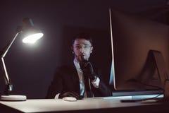 портрет агента шпиона показывая знак безмолвия на таблице с экраном компьютера стоковое фото rf