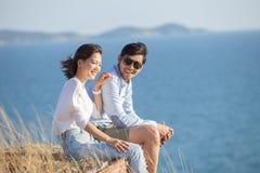 Портрет азиатских каникул молодого человека и женщины расслабляющих на море Стоковое Изображение RF