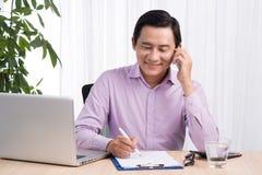 Портрет азиатского бизнесмена говоря на мобильном телефоне в офисе Стоковое Изображение
