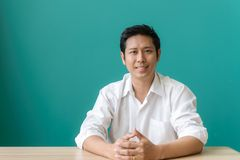 Портрет азиатского бизнесмена усмехаясь и смотря камеру с улыбкой пока сидящ на его месте службы голубой стены Стоковая Фотография RF