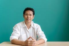 Портрет азиатского бизнесмена усмехаясь и смотря камеру с улыбкой пока сидящ на его месте службы голубой стены Стоковые Изображения RF