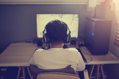 Портрет азиатского gamer мальчика играя игры на компьютере в комнате дома стоковые фотографии rf