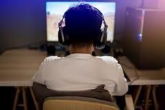 Портрет азиатского gamer мальчика играя игры на компьютере в комнате дома стоковые изображения
