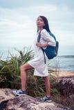Портрет азиатской женщины с рюкзаком в белом платье взбираясь на горе около моря Стоковое Изображение RF