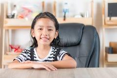 Портрет азиатской маленькой девочки сидя на деревянном столе Стоковая Фотография RF