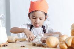 Портрет азиатской маленькой девочки держа тесто в руке и хлебопекарне o стоковая фотография