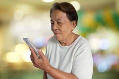 Портрет азиатской пожилой женщины усмехаясь с использованием мобильного телефона и красочной предпосылки bokeh стоковые изображения