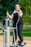 Портрет активной жирной женщины без комплексов включен на stepper имитаторе стоковое фото