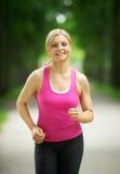 Портрет активной молодой женщины jogging в парке Стоковые Изображения RF