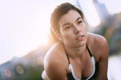 Портрет активной millenial женщины jogging на сумраке с городскими городским пейзажем и заходом солнца на заднем плане Стоковые Изображения