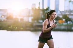 Портрет активной millenial женщины jogging на сумраке с городскими городским пейзажем и заходом солнца на заднем плане Стоковые Фотографии RF