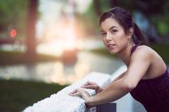 Портрет активной millenial женщины jogging на сумраке с городскими городским пейзажем и заходом солнца на заднем плане Стоковое Изображение
