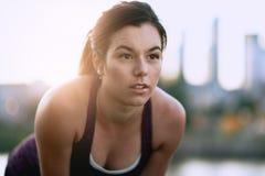 Портрет активной millenial женщины jogging на сумраке с городскими городским пейзажем и заходом солнца на заднем плане Стоковая Фотография RF