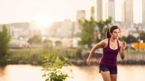 Портрет активной millenial женщины jogging на сумраке с городскими городским пейзажем и заходом солнца на заднем плане Стоковые Изображения RF