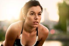 Портрет активной millenial женщины jogging на сумраке с городскими городским пейзажем и заходом солнца на заднем плане Стоковое Изображение RF