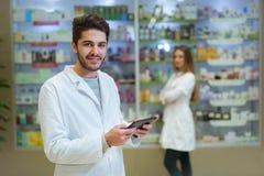 Портрет аптекаря держа цифровую таблетку в фармации Стоковое фото RF