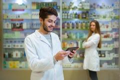 Портрет аптекаря держа цифровую таблетку в фармации Стоковые Изображения RF