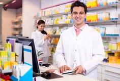 Портрет аптекаря и ассистентской работы Стоковое фото RF