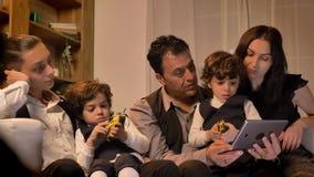 Портрет арабской семьи сидя на кресле и наблюдая заинтересованно в планшет в живя комнате в уютной атмосфере видеоматериал