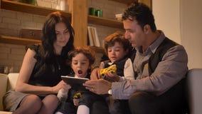 Портрет арабской семьи сидя совместно на кресле и наблюдая в планшет в живя комнате в уютной атмосфере акции видеоматериалы