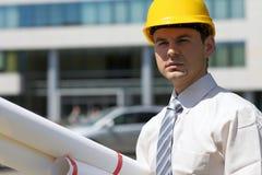 Портрет архитектора в защитном шлеме держа светокопию на строительной площадке Стоковое Фото