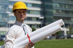 Портрет архитектора в защитном шлеме держа светокопию на строительной площадке Стоковые Фотографии RF