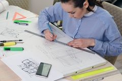 Портрет архитектора женщины на работе на дизайн-проекте здания, на бумаге таблицы, правители, карандаши, компас, smartphone, twis Стоковое фото RF