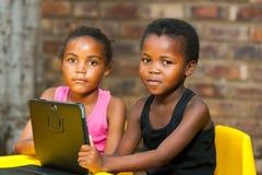 Портрет 2 африканских малолеток с цифровой таблеткой. Стоковое Фото