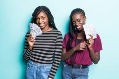Портрет 2 африканских услаженных девушек радуясь выигрыш и танцуя пока держащ вентиляторы денег наличных денег изолированный над  стоковое изображение rf