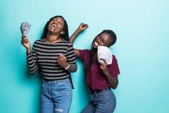 Портрет 2 африканских услаженных девушек радуясь выигрыш и танцуя пока держащ вентиляторы денег наличных денег изолированный над  стоковая фотография rf