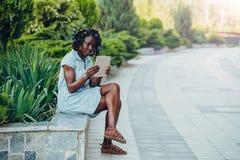 Портрет африканской усмехаясь молодой чернокожей женщины сидя в парке и используя цифровой планшет смотря экран стоковое изображение