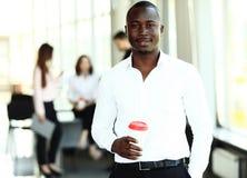 Портрет Афро-американского бизнесмена при исполнительные власти работая в предпосылке Стоковое фото RF