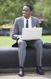 Портрет Афро-американского бизнесмена работая на компьтер-книжке outdoors Стоковая Фотография