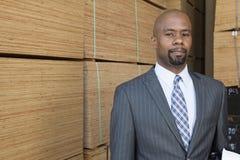 Портрет Афро-американского бизнесмена стоя перед штабелированными деревянными планками Стоковая Фотография RF
