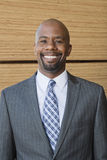 Портрет Афро-американского бизнесмена усмехаясь с штабелированными деревянными планками в предпосылке Стоковое фото RF