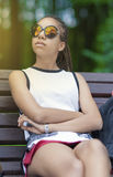 Портрет Афро-американского девочка-подростка при длинные Dreadlocks представляя в парке Outdoors в солнечных очках Стоковое фото RF