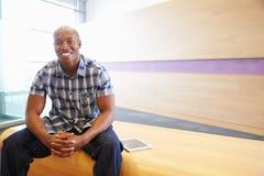 Портрет Афро-американского усаживания человека, смотря к камере Стоковая Фотография RF