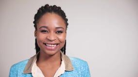 Портрет афро американской девушки смотря камеру и улыбки обширно акции видеоматериалы
