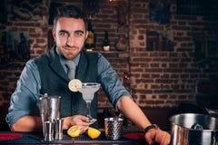 Портрет бармена делая коктеили, питье маргариты подписи на местном баре Стоковые Изображения