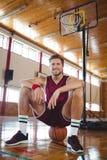 Портрет баскетболиста сидя на шарике Стоковые Фотографии RF