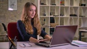 Портрет белокурой кавказской коммерсантки работая внимательно с ноутбуком в офисе выделяет глубоко для того чтобы выразить gladne видеоматериал