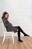 Портрет беременного женского усаживания на стуле Стоковые Фото