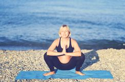 Портрет беременной азиатской женщины делая йогу в береге моря стоковое изображение