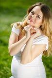 Портрет беременной женщины сидя на траве Стоковое Изображение