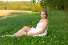Портрет беременной женщины сидя на траве Стоковая Фотография RF