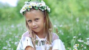 Портрет Белокурая девушка, ребенок, сидит в траве, среди маргариток, в луге стоцвета Она восхищает маргаритки акции видеоматериалы
