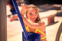 Портрет белокурой девушки в бикини на имитаторе на земле спорт Стоковое фото RF